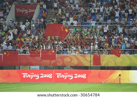 SHENYANG, CHINA - AUGUST 10: Spectators cheer the Chinese team prior to the start of a match between China and Belgium at the Beijing Olympic Games soccer tournament August 10, 2008 in Shenyang, China - stock photo