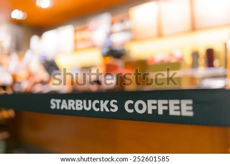 SHENZHEN, CHINA - JANUARY 31, 2015: Starbucks Cafe interior at night. Starbucks Corporation is an American global coffee company and coffeehouse chain based in Seattle, Washington  - stock photo