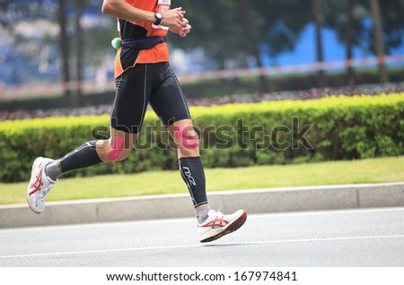 SHENZHEN - DEC 08: Unidentified athlete(number10774 ) running at the shenzhen international marathon 2013, shennan road,shenzhen city,China,on DEC 08,2013 at Shenzhen city,Guangdong province,China.