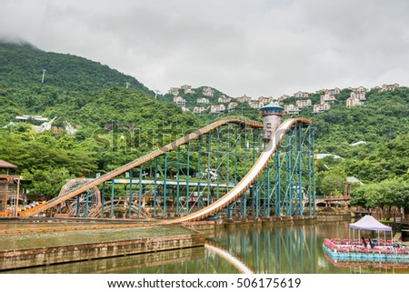 Shenzhen, Guangdong, China- September 16, 2016: Editorial: People sitting on boat doing extreme sport water slide with splash on the track in park of Overseas Chinese Town East (OCT East)