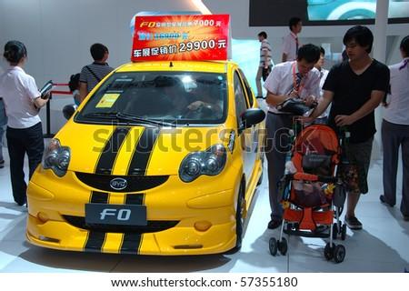 SHENZHEN - JUNE 14: Shenzhen-Hong Kong-Macao Auto Show, family watching BYD cars on June 14, 2010 in Shenzhen. - stock photo