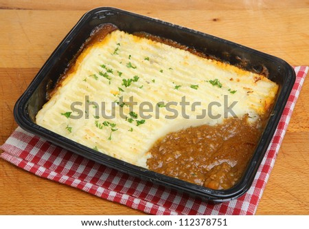 Shepherds pie convenience food in plastic tray with steam rising. - stock photo