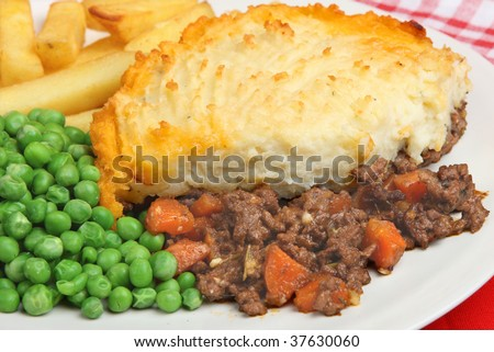 Shepherds pie with chips and peas - stock photo