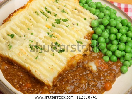 Shepherds pie with garden peas. - stock photo