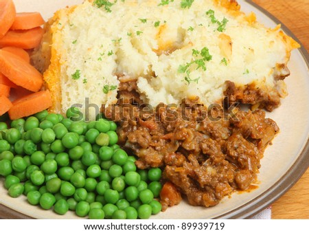 Shepherds pie with peas and carrots. - stock photo