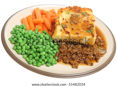 Shepherds pie with peas, carrots and gravy. - stock photo