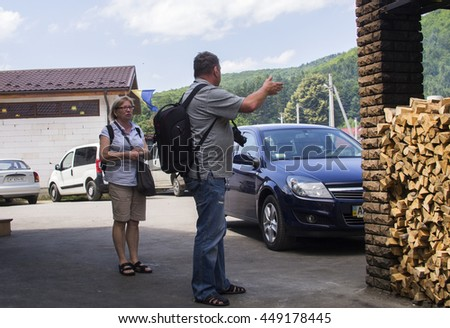 SHEPIT, KOSIV DISTRICT, IVANO-FRANKIVSK REGION, UKRAINE - July 12, 2015: Tourists on a rural street - stock photo