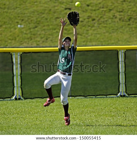 SHERBROOKE, CANADA - August 6: New Brunswick's Melissa Kenny makes a catch in women's softball at the Canada Games August 6, 2013 in Sherbrooke, Canada. - stock photo