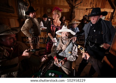Sheriff and cowboys with weapons on cheating gambler - stock photo