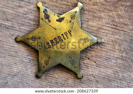 Sheriff badge on rustic wooden background - stock photo