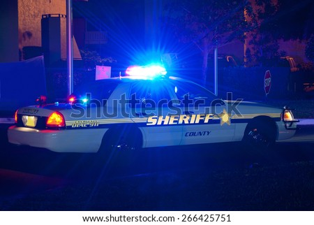 Sheriff cruiser car with his lights on at night on a call to protect the peace - stock photo