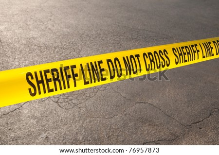 Sheriff line do not cross - caution tape in urban environment