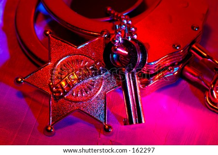 Sheriffs Badge and Handcuffs With Colored Gel Lighting - stock photo