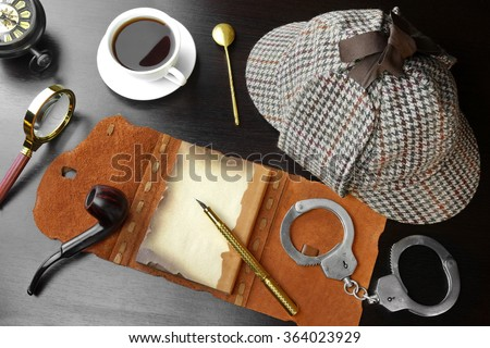 Sherlock Concept. Private Detective Tools On The Black Wood Table Background. Deerstalker Hat, Opened Notebook With Blank Brown Page, Pipe, Magnifying Glass, Cuffs, Fountain Pen. Overhead View - stock photo