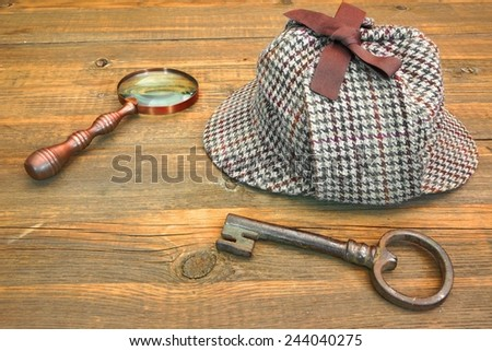 Sherlock Holmes Cap famous as Deerstalker, Old Key and Retro Magnifier on Grunge Wooden Table - stock photo