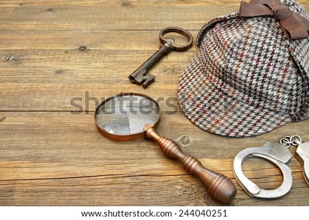Sherlock Holmes Cap famous as Deerstalker, Old Key, Real Handcuffs and Vintage Magnifying Glass on Grunge Wooden Table - stock photo