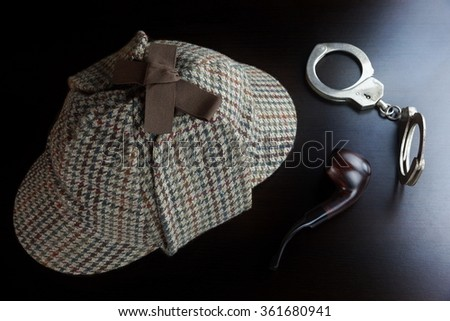 Sherlock Holmes Deerstalker Hat Smoking Pipe And Handcuffs On The Black Wooden Table Background. Overhead View.  Investigation Concept. - stock photo
