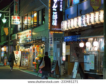 SHIBUYA, TOKYO - JANUARY 10, 2014: Bar street illuminated with neons at night in Shibuya, downtown Tokyo. One of the most popular and biggest commercial district in Japan. - stock photo