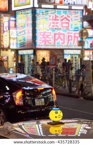 SHIBUYA, TOKYO, JAPAN - AUGUST 2015: Neon Tokyo taxi sign in a Shibuya street at night, with a busy night scene in the background. - stock photo