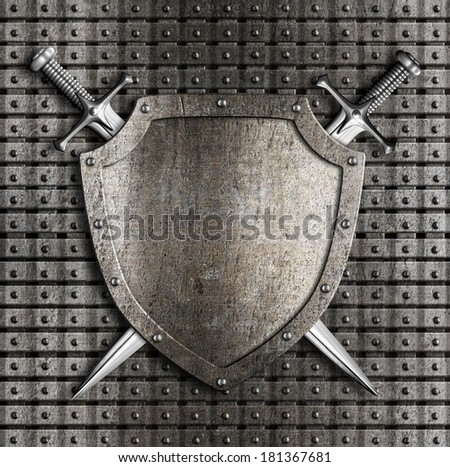 Shield and two swords crossed hanging on metal wall with rivets - stock photo