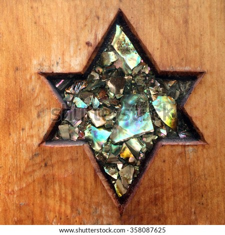 Shield of David or Star of David curved on wood decorated with ormer shells (Paua) - stock photo