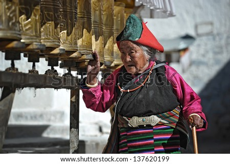 SHIGATSE - MAY 3: Tibetan pilgrim circles the holy Tashilunpo monastery on May 3, 2013 in Shigatse. Some devotees walk 108 times around the monastery to accumulate merit (karma).