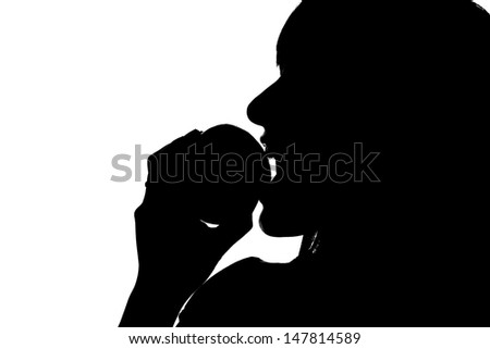 Shiluette of a young woman biting into an apple