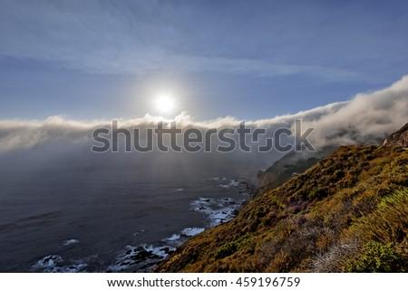 Shimmering blue, aquamarine sea and misty sky, the sun setting along steep sheer jagged cliffs of the Big Sur Coastline, while waves are splashing on huge rocks. Photographed near Carmel California - stock photo