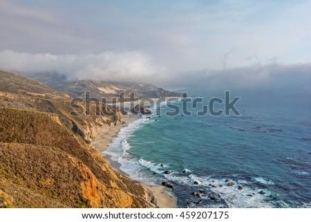 Shimmering blue, aquamarine sea and misty sky, the sun setting along steep sheer jagged cliffs of the Big Sur Coastline, while waves are splashing on huge rocks. Photographed near Carmel California. - stock photo