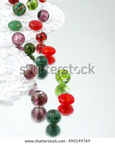 Shimmering glass beads and vintage lace on mirror background