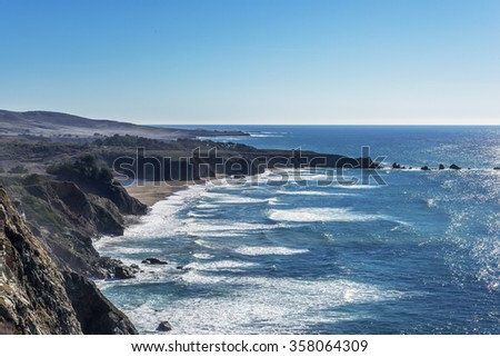Shimmering reflective sunlight, blue skies, offshore rocks & waves splashing along the rugged Big Sur coastline, viewed from jagged cliffs of Ragged Point by Highway 1 on the California Central Coast. - stock photo