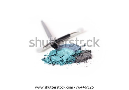 Shimmery metallic eyeshadow in smoky blues, smashed and shown with brushes on an isolated white background.