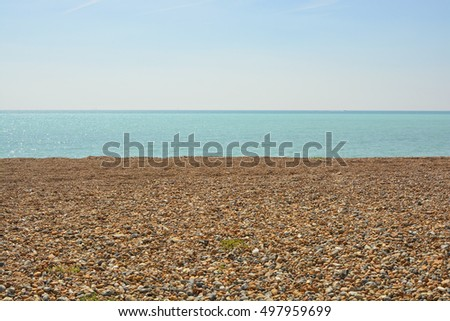 Shingle beach with sea and horizon beyond. Worthing in West Sussex, England