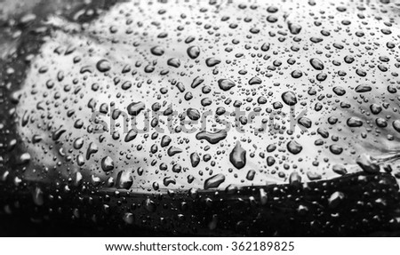 Shining black metallic car hood with raindrops, closeup photo with selective focus and shallow DOF