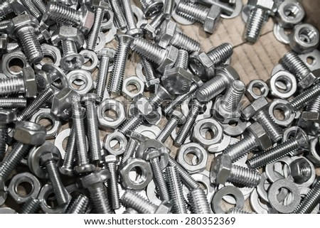 Shining bolts and nuts in a cardboard box, photo background with selective focus  - stock photo