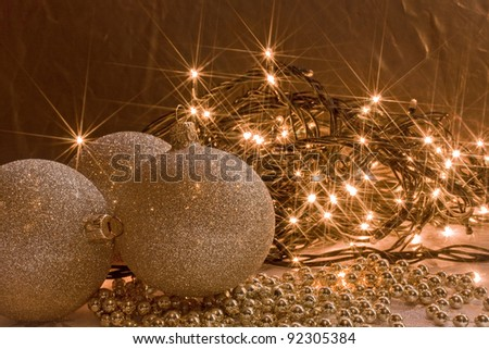 shining golden ornaments and Christmas lights garland - stock photo