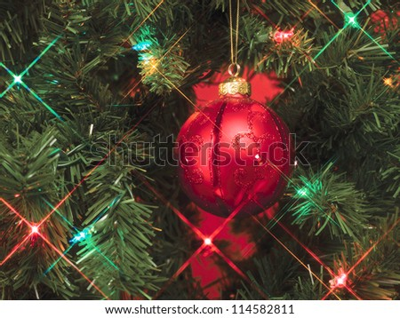 Shining lights and bauble on a Christmas tree - stock photo