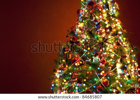 shining lights of a Christmas tree on red background - stock photo