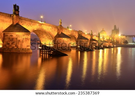 Shining lights on Charles bridge across Vltava river in foggy autumn evening, Prague, Czech Republic - stock photo