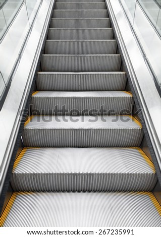 Shining metal escalator moving up, vertical photo with perspective effect - stock photo
