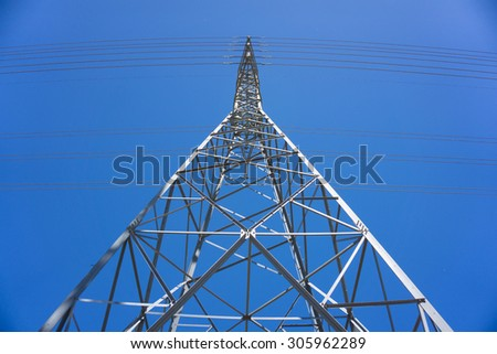 Shining profile of tall electric tower under a bold blue sky. - stock photo