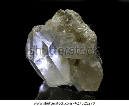 Shining rock crystal with reflections on black background - stock photo