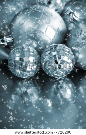 Shining silvery ornaments on a reflective background surrounded by snowflakes.