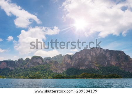 Shining sun at Ratchaprapha Dam at Khao Sok National Park, Suratthani, Thailand. Beautiful mountains and sky. - stock photo
