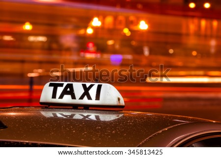 Shining Taxi inscription against passing cars on night street of big cit - stock photo