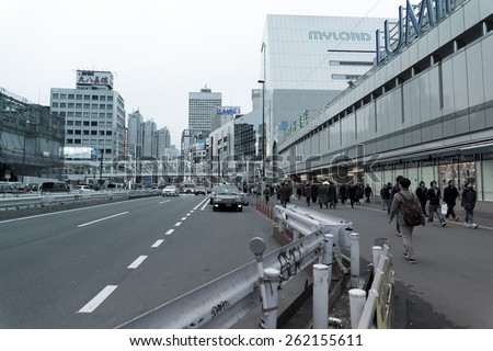 SHINJUKU, TOKYO - FEB 13 : People on the street  of  Shinjuku, downtown Tokyo on February 13, 2015. About 800,000 people live and work here. The biggest commercial and night life town in Japan. - stock photo