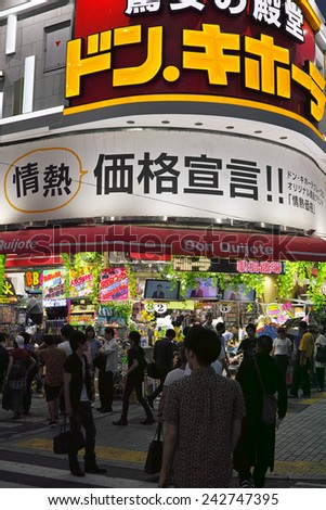 SHINJUKU, TOKYO - MAY 31, 2014: Street view of Shinjuku commercial district at night, billboards with neon light and crowd of pedestrians. - stock photo