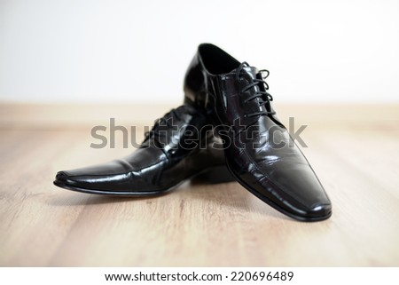 Shinny black mans shoes on the floor - stock photo