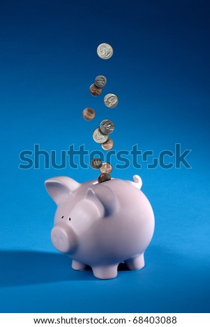 shiny American coins dropping into a pink piggy bank shot on blue background with space for copy - stock photo