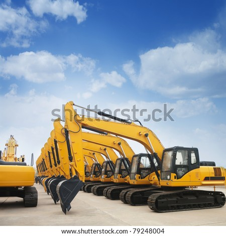 shiny and modern yellow excavator machines - stock photo